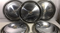 5 Cadillac hubcaps and emblems
