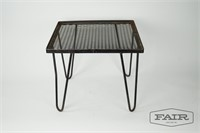 Metal end table with hairpin legs and red carpet