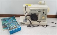 Singer sewing machine with accessories and book