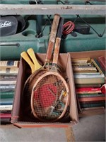 Box of old tennis rackets and ping pong paddles