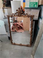 Very ornately framed wall mirror