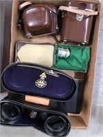 Box of binoculars in case, camera in case, lens