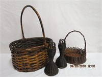 2 wicker baskets and a pair of wicker candle