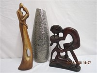 2 carved wood figures and a silver colored vase