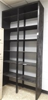 Painted black wooden tall shelving unit. B
