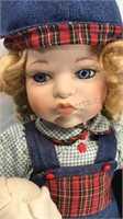 Seated Porcelain Doll with denim overalls hat and