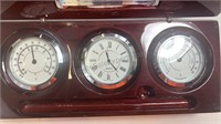 Wooden case holding a thermometer, clock,