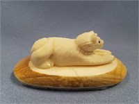 Carved ivory husky on a section of whale's tooth