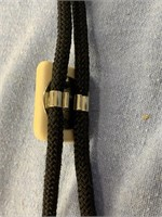 Ivory bolo tie with relief carved gold miner with
