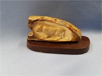 Relief carved fossilized ivory lynx mounted on a h