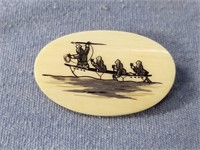 Fossilized mastodon scrimshaw pin of a hunting sce