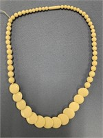 Ivory beaded necklace with flat graduated beads, t