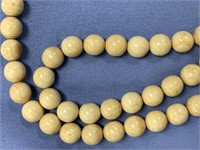 String of fossilized ivory beads with scrimmed ivo