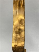 Fossilized ivory artifact with relief carving of a