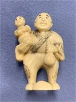 Ivory netsuke of a man holding a wine jug and chil