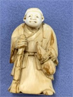 "Ivory netsuke of a man with cane and wine jug 2"" t"