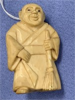 Ivory Japanese style carving of man holding broom,