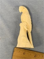 Moose antler section carved into a parrot on a tre