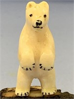 Ivory carving of a standing bear on black ivory ba