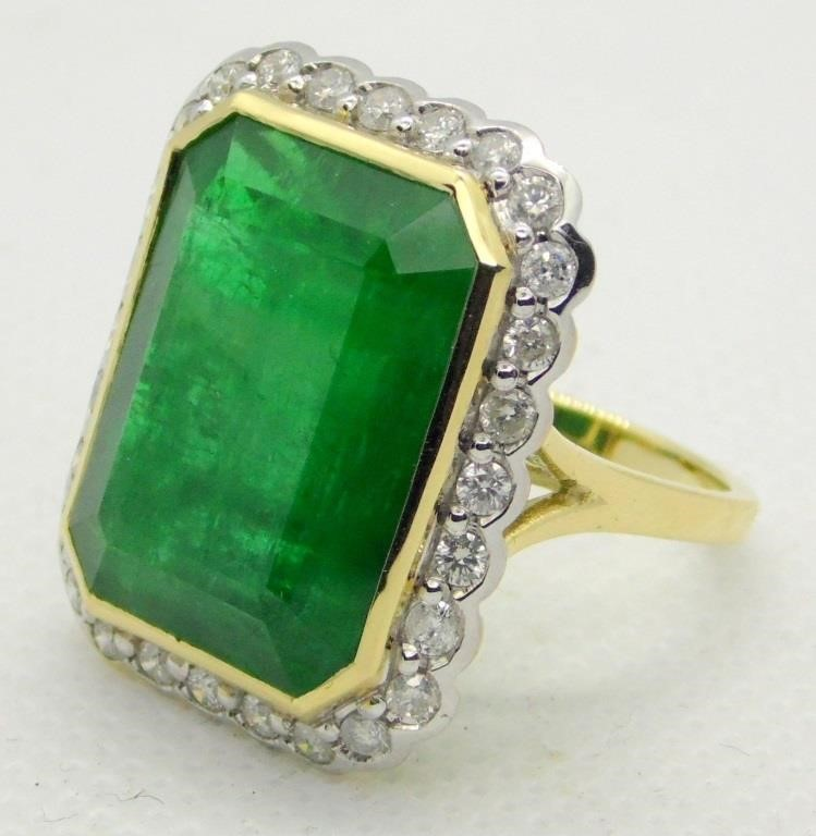 Fabulous 20.75 ct Zambian Emerald & Diamonds Cocktail Ring . The very large central vivid deep green Zambian emerald (20.75 ct),bezel set,with 28 round brilliant cut diamonds (0.82 ct TDW),grain set. All mounted and marked .585 Yellow & White Gold. Size (M 13). Boxed.W.G.I. Certificate Estimated retail £32600