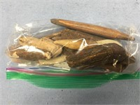 Bag of fossilized bone and ivory artifacts and scr