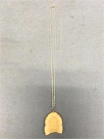 Fossilized ivory pendant with relief carved halibu