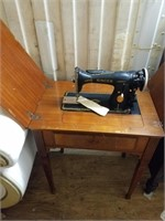 Singer electric sewing machine on wood cabinet, le