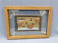 Framed window pane with a portion of hand woven