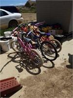3 girls bikes, 1 boys bike and a 2 bike bicycle