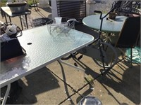 Two patio tables, exerciser, content on tables