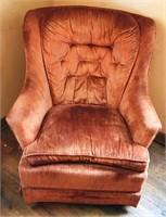Orange swiveling rocker chair