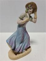 Porcelain woman holding hat against wind figure