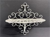 Scrolling white metal wire shelf