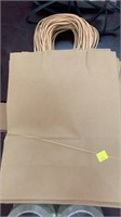 Stack of 24 brown paper gift bags