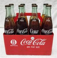 (8) pintsize Coke bottles in red plastic carriers