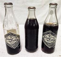 (3) Coca-Cola bottles