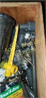 Wooden box full of lawn Sprinklers and parts