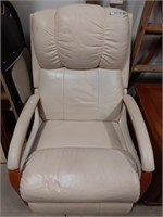 White leather like recliner and plaid foot rest on