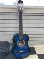Blue acoustic guitar with guitar bag and