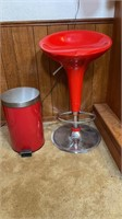Red stool and trash can