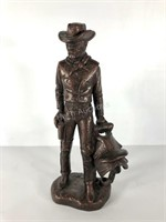 Bronzed cowboy and saddle statue by Austin