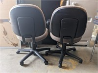 Two cushioned adjustable swivel chairs. One with