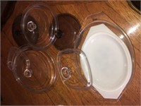 Pyrex measuring cups and assorted glass lids